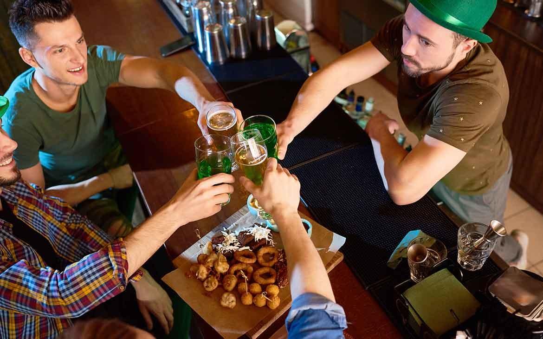 Homens vestidos de verde segurando copo com cerveja brindam em mesa de bar o Saint Patrick 's Day, data comemorada na Irlanda