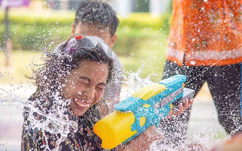 """Mulher sorri enquanto dispara arminha de água em uma luta de água, conhecida como """"Songkran"""", um dos festivais mais divertidos do mundo, que acontece na Tailândia"""