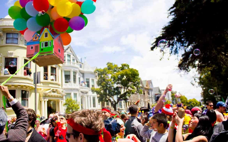 Pessoas vestidas com roupas coloridas conversam, riem, sopram bolinhas de sabão e carregam balões coloridos durante Bay to Breakers uma ocorrida anual que acontece em São Francisco