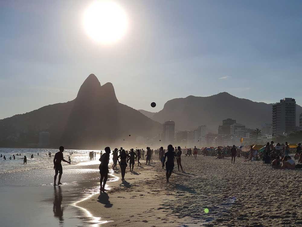 Silhueta de pessoas jogando bola em areia de praia no Rio de Janeiro, durante o dia