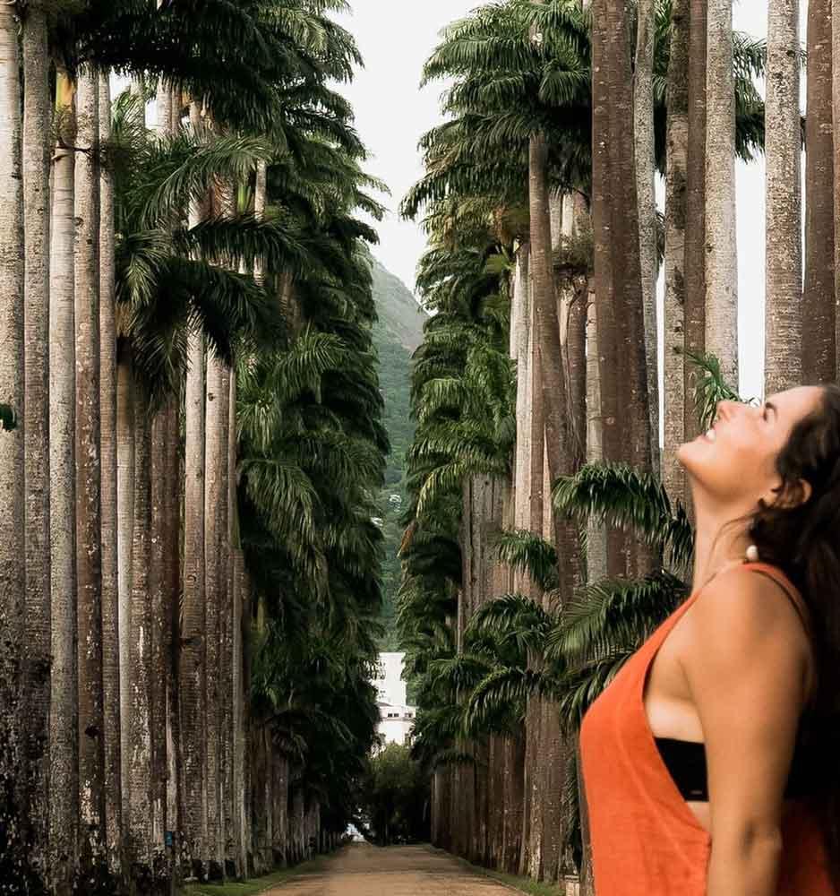 Mulher vestindo uma blusa laranja, sorri de cabeça erguida. Ao fundo, há o corredor de palmeiras imperiais do Jardim Botânico, um dos melhores passeios do rj