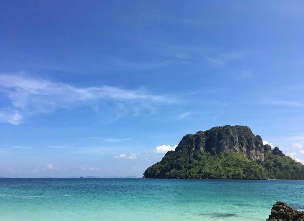 Mar azul, durante o dia, onde ao fundo há uma montanha, em Ao Nang, cidade da Tailândia, um dos lugares para viajar barato.