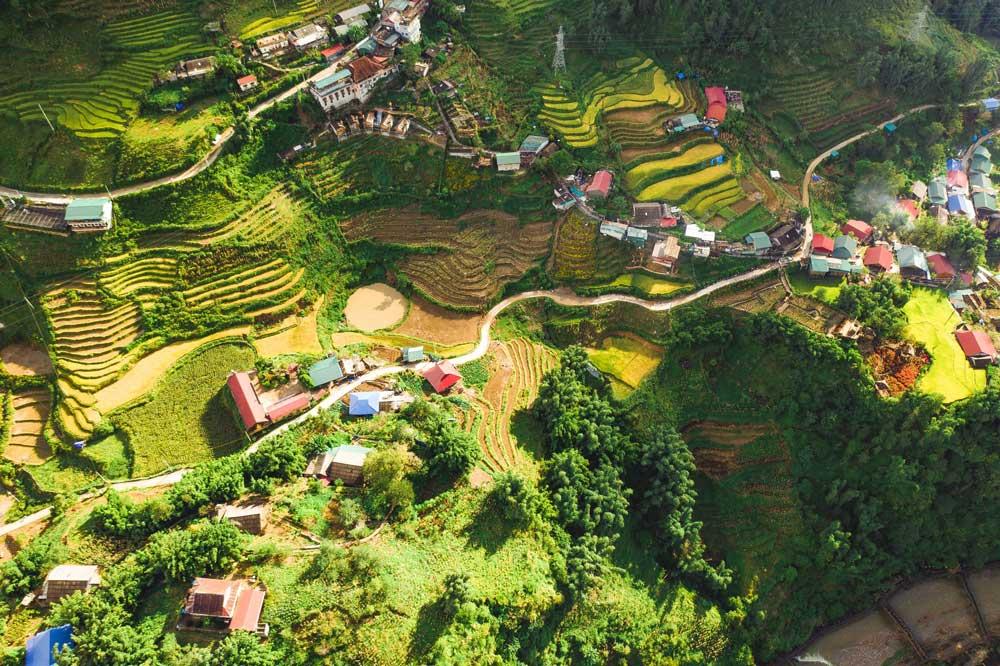 Vista aérea de casas coloridas, estrada e vegetação de cidade no Vietnã, um dos melhores lugares para viajar barato