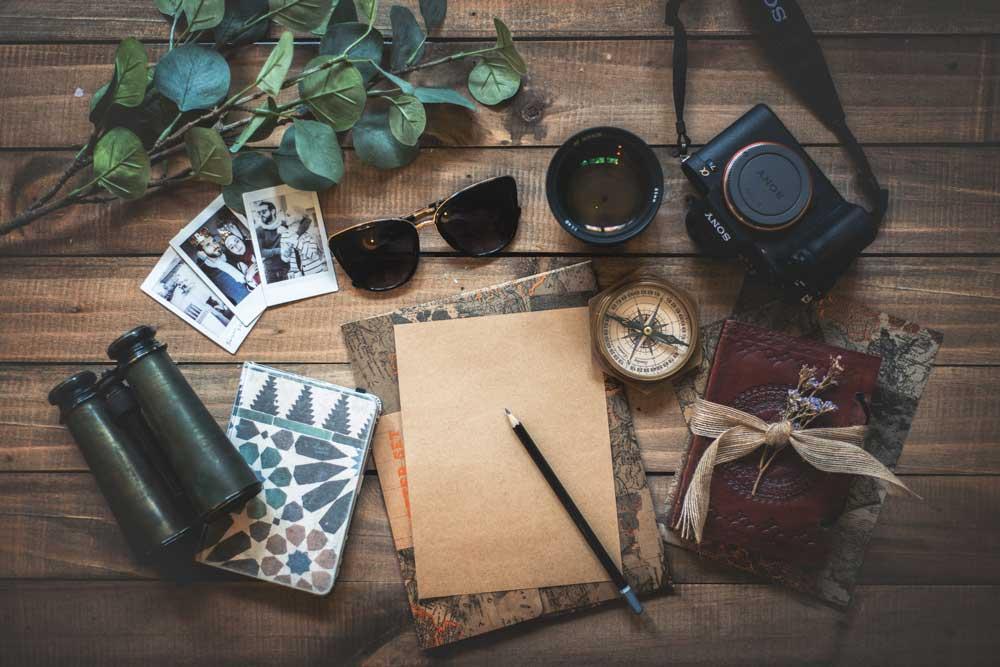 Mesa de madeira onde estão espalhados uma câmera fotográfica, um binóculos, cadernos, uma folha de papel em branco com um lápis em cima, um óculos, fotografias de um casal e plantas.