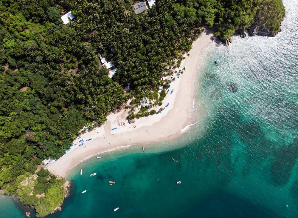 Vista área, durante o dia, do mar, e vegetação da Ilha Tortuga, localizada no Haiti, um dos lugares para viajar barato