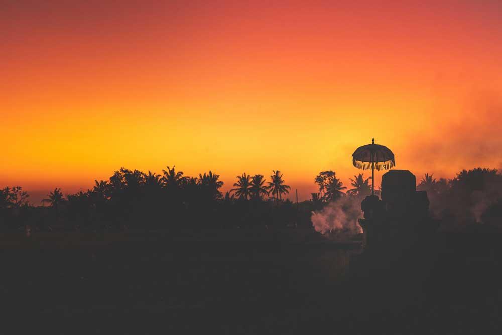 Silhueta de palmeiras ao pôr do sol em Bali, um dos melhores lugares para viajar barato.