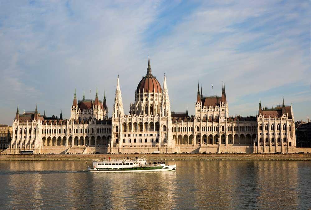 Vista panorâmica de edifícios legislativos de 1885 que fazem parte do Parlamento da Hungria, às margens do rio, onde há um barco, em Budapeste.