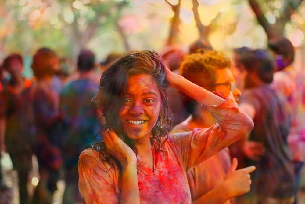 Mulher sorridente com a mão na cabeça e no cabelo, durante o dia, em festa na Índia, um dos lugares para viajar barato.