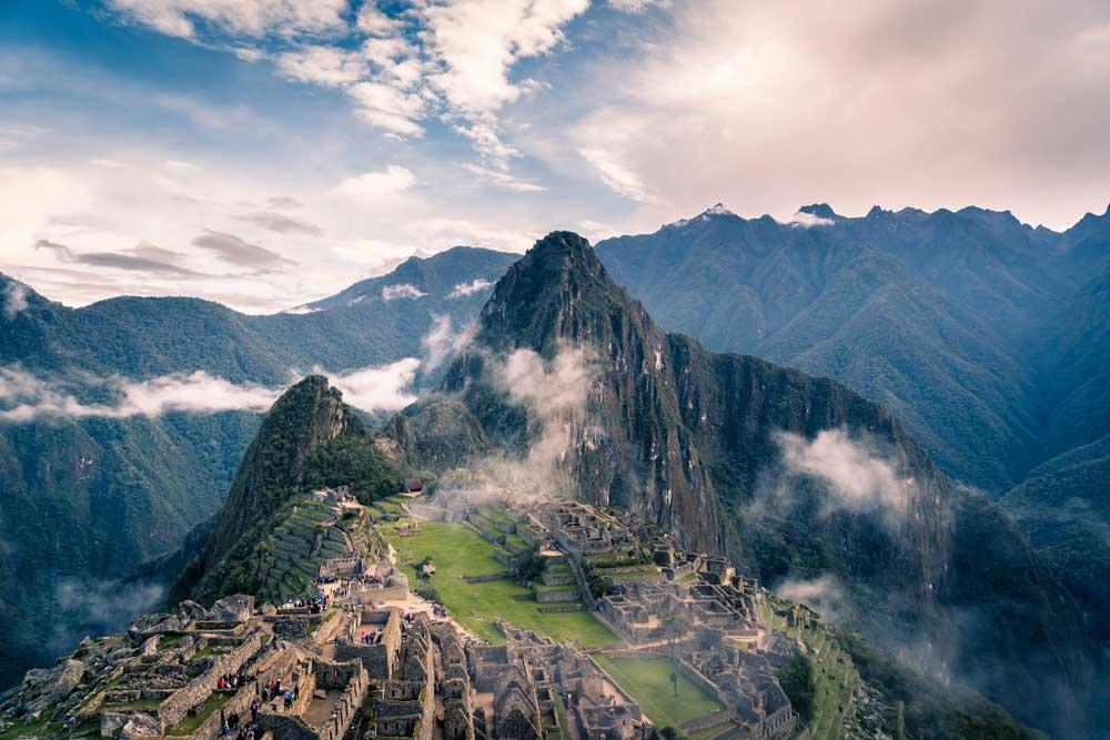 Vista áerea de Machu Picchu, durante o dia, uma cidade no Peru, rodeada por montanhas, repleta de muralhas de pedra e construções do século XV, em um dos lugares para viajar barato