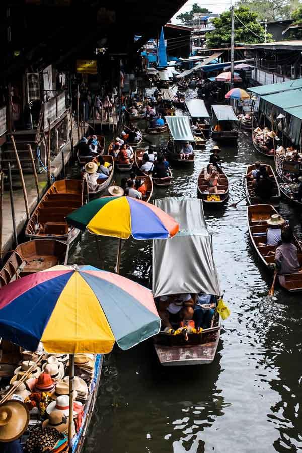 Pessoas andando de barco no rio, durante o dia, perto do mercado flutuante um dos atrativos em meio há muito o que fazer em Bangkok em 3 dias