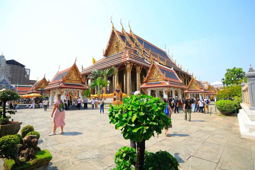 Pessoas caminham, durante o dia, em frente a templos laranja, que são bons atrativos para quem busca o que fazer em Bangkok