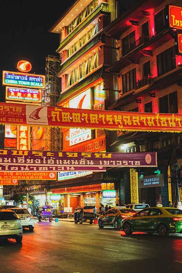Carros circulam na rua em Bangkok, durante a noite, onde há faixas coloridas estendidas, e construções com letreiros iluminados