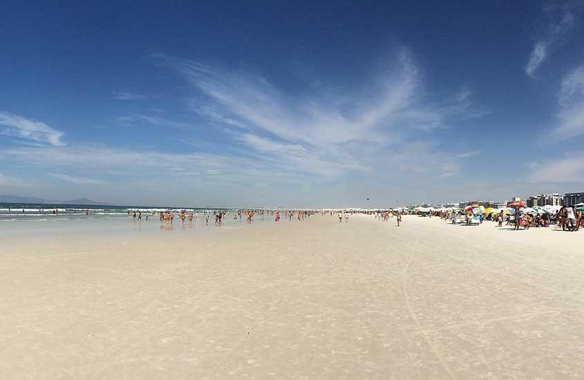 pessoas em areia de praia em Cabo Frio, durante o dia, sob o céu azul