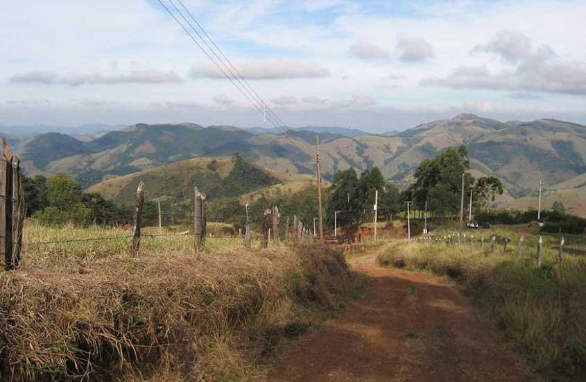 Estrada de terra durante o dia, que leva a São Francisco Xavier, com montanhas da Serra da Mantiqueira e céu azul ao fundo.