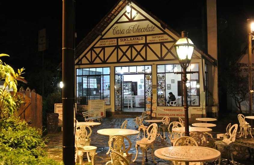Mesas e cadeiras ao ar livre durante a noite em frente à Casa do Chocolate, uma loja de chocolates artesanais em Penedo, uma opção de passeio no turismo na Serra da Mantiqueira