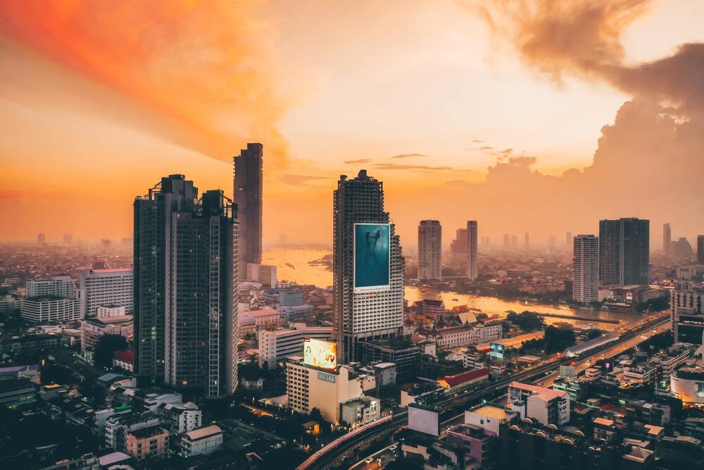 Vista área de arranha-céus, durante o pôr do sol, em Bangkok, um dos destinos para você conhecer se for viajar para para Tailândia