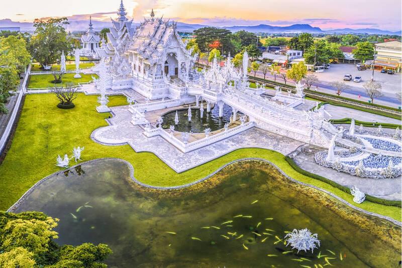 Construção branca no estilo de um templo budista, conhecida como Wat Rong Khun (Templo Branco), ao lado de gramado e lago, durante o entardecer