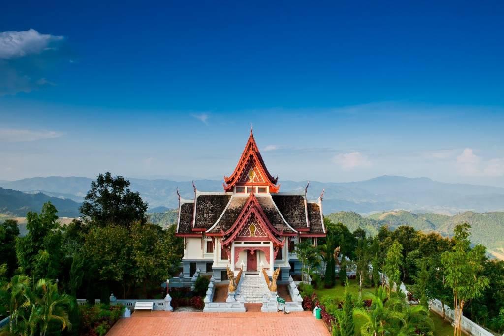 Construção branca e cinza com telhado vermelho, em meio a árvores e montanhas sob o céu azul, durante o dia, em Chiang Rai, um dos destinos para conhecer se você for viajar para Tailândia
