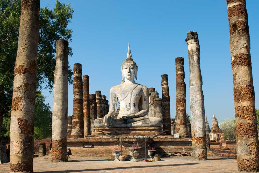 estátua do buda sentado com pernas cruzadas sob céu azul, em parque de histórico de Sukhothai, no norte da Tailândia