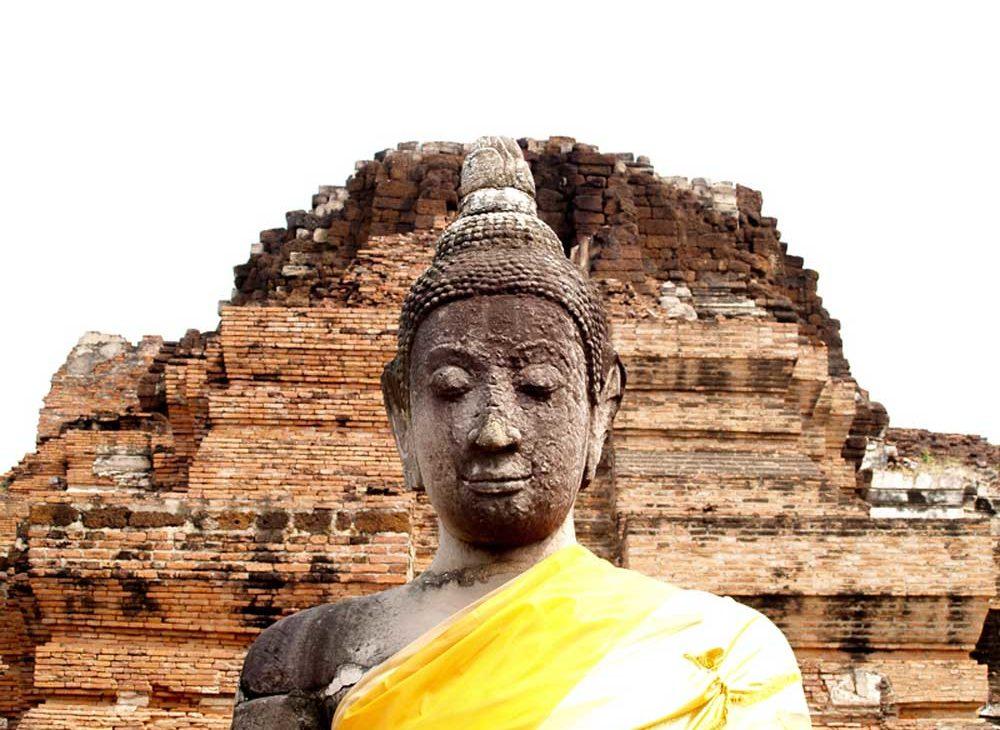 Estátua do buda do pescoço para cima, com olhos fechados, em frente a templos em ruínas, durante o dia, em Ayutthaya, cidade ideal para quem quer viajar para a Tailândia para conhecer a história do país