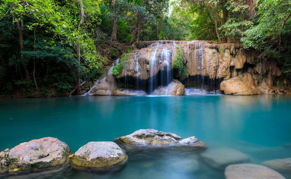 Águas cristalinas de Cataratas do Erawan, durante o dia, em Kanchanaburi, localizada na Tailândia Central