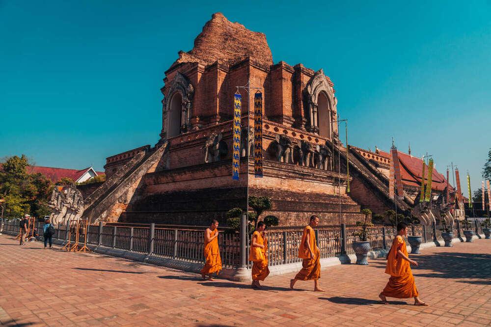 Homens monges vestidos de laranja caminham, durante o dia, em frente a um templo de tijolos vermelhos em Chiang Mai, norte da Tailândia