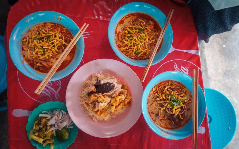 5 pratos azuis e rosas, com comida e hashis em cima, em uma mesa com uma toalha vermelha