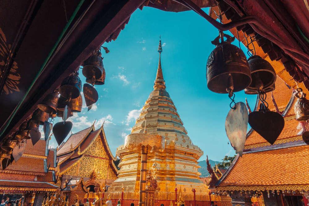 Construções douradas e com telhados laranjas, durante o dia, sob o céu azul em Chiang Mai