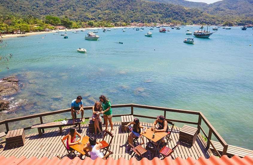 viajantes conversam em deck de hostel em Ilha Grande em frente ao mar