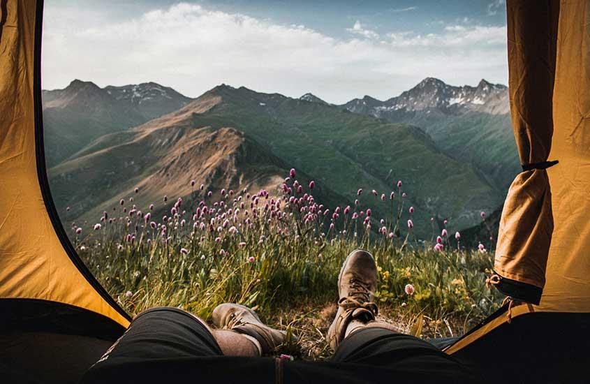 viajante deitado em barraca de camping, um meio de economizar na hospedagem e viajar barato