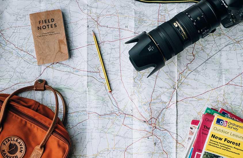 Câmera fotográfica, caderno de anotações e lápis em cima de mapa de papel