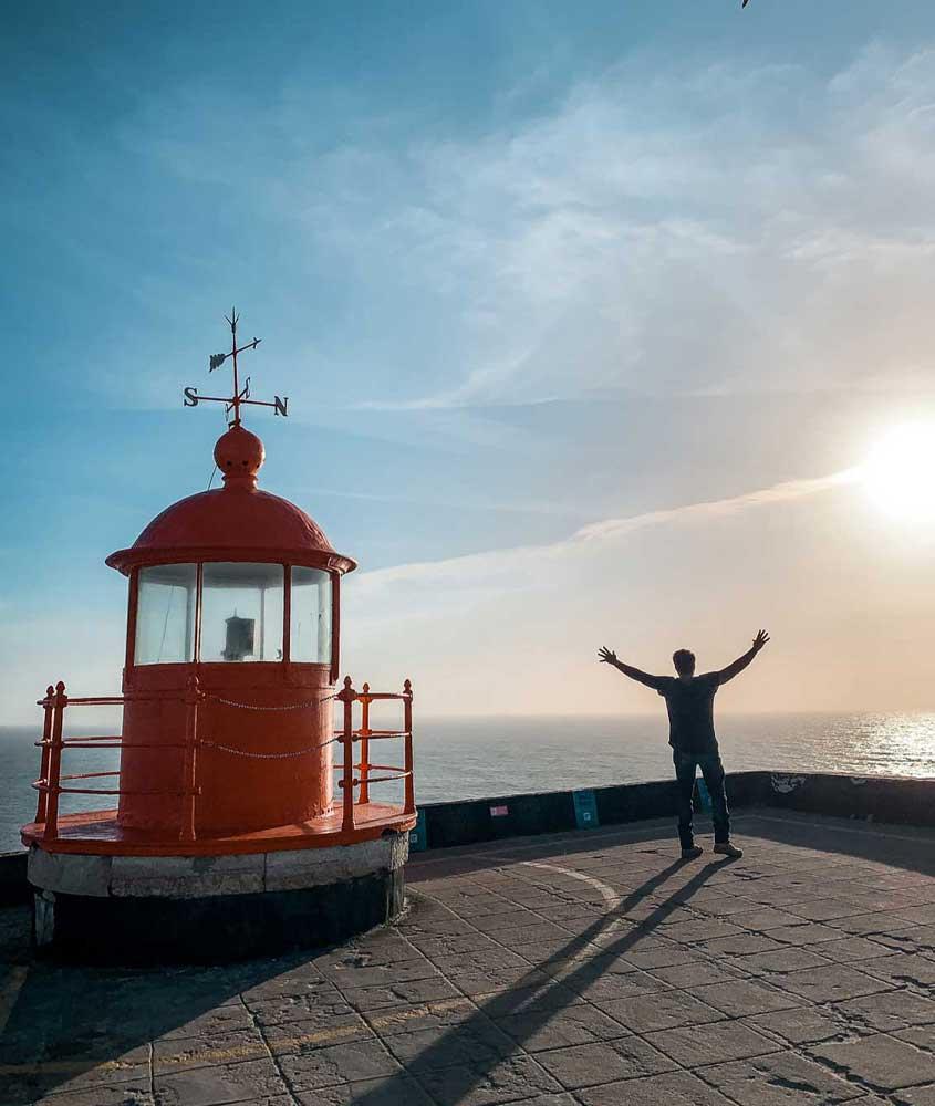 viajante de braços abertos em mirante em frente ao mar uma atração gratuita, boa para quem quer viajar barato