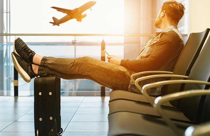 viajante sentado em aeroporto observa avião decolar
