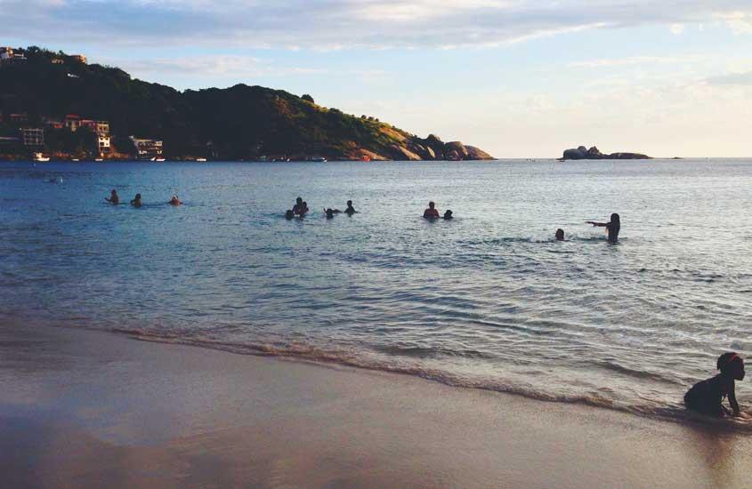 Pessoas tomando banho de mar durante o dia, uma das opções entre muito o que fazer em Barra de Guaratiba