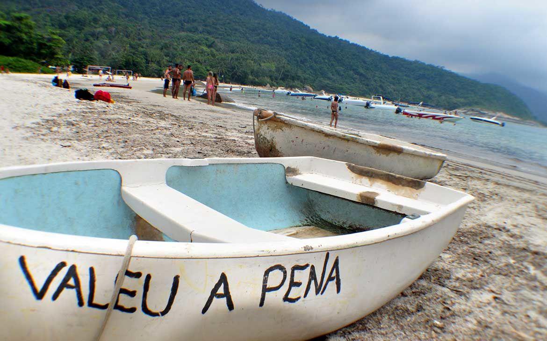 Pequeno barco branco em praia de Ilha Grande, onde há escrito ''valeu a pena''
