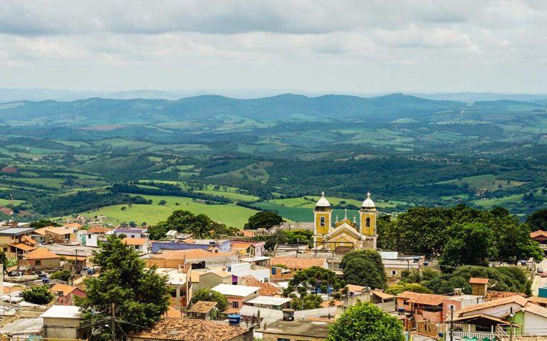 vista aérea de construções, igreja e montanhas de São Thomé das Letras