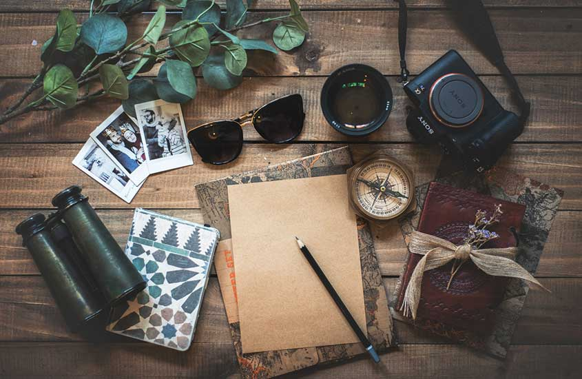 câmera, caderno, fotos, óculos, em cima de mesa de madeira