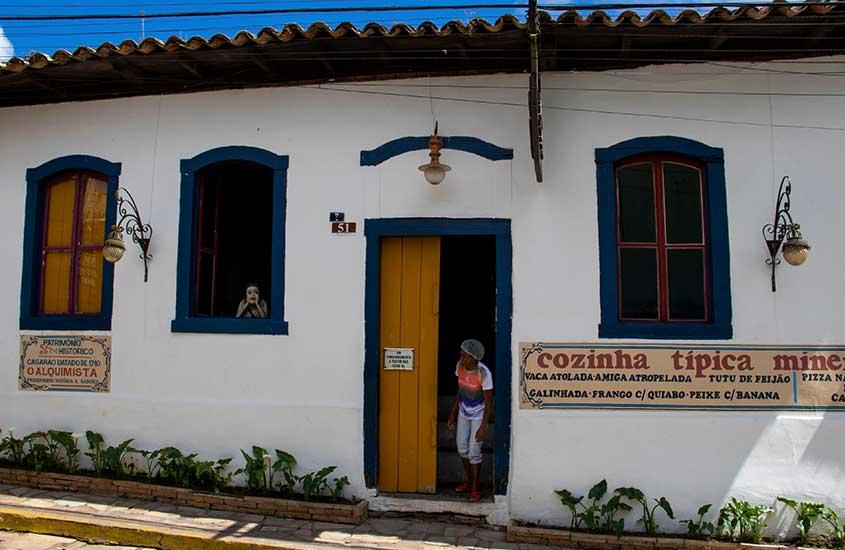 cozinheira, parada em porta de restaurante, olha para rua em São Thomé das Letras