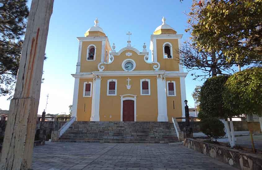 Igreja amarela e branca sob o céu azul, um dos lugares para conhecer entre muito o que fazer em São Thomé das Letras