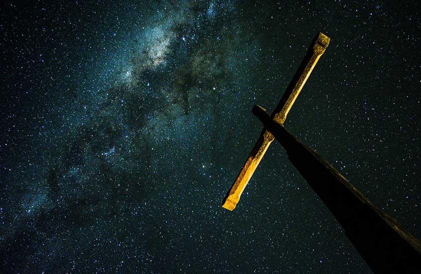 cruz sob céu estrelado durante a noite em São Thomé das Letras