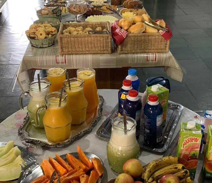 sucos, pães e frutas em mesa de café da manhã da Pousada Mirante das Pedras