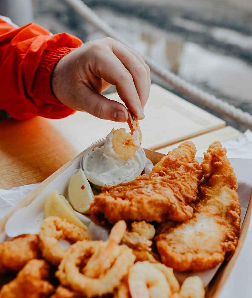 viajante come fish and chips, uma das comidas típicas da nova zelandia