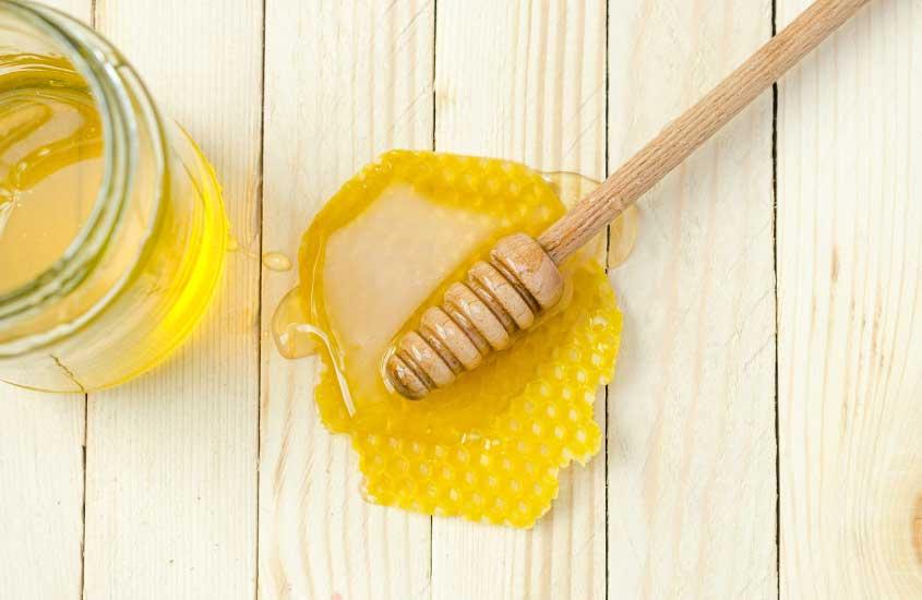 manuka honey, um mel famoso da nova zelandia, em cima de mesa de madeira