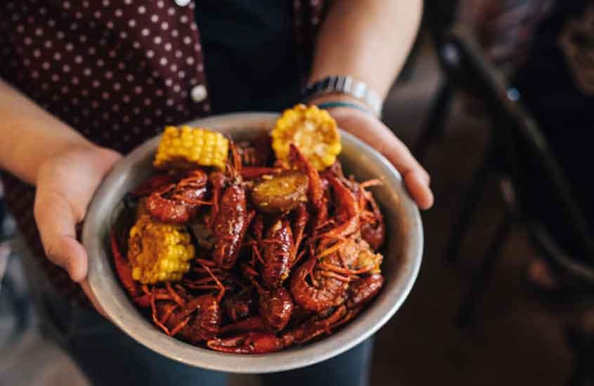 viajante segura prato com lagostins, uma das comidas típicas da nova zelandia