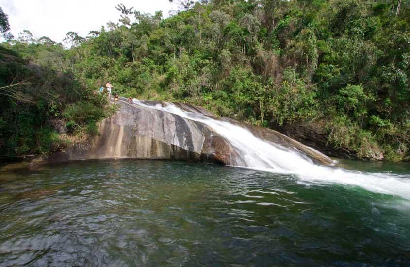 pessoas escorregam em cachoeira em Visconde de Mauá, um dos lugares para viajar no estado do rio de janeiro