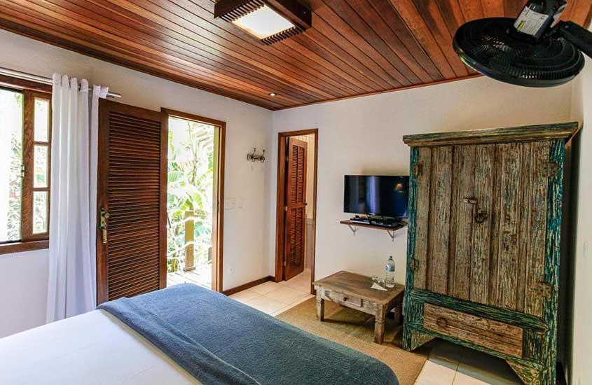 cama, guarda-roupa e tv em quarto aconchegante de Atlantiga Jungle Ladge uma boa opção para quem busca onde ficar em ilha grande
