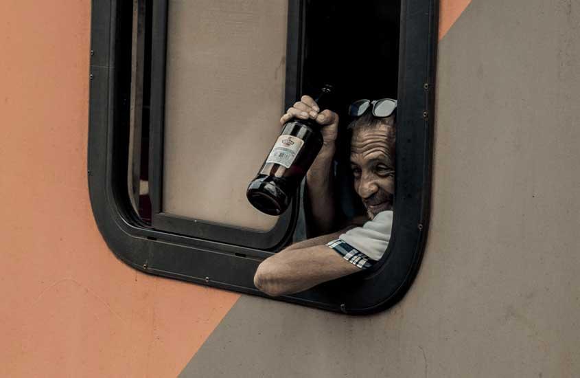 homem em ônibus, segura garrafa de cerveja. Uma das curiosidades da África do Sul é que não é tão fácil assim comprar bebidas alcoólicas