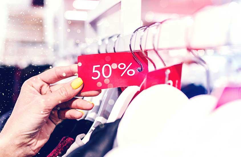 turista segura etiqueta de roupa com 50% de desconto