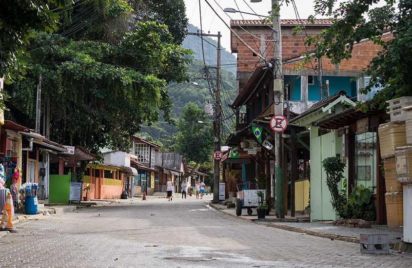 pessoas caminham em rua de Vila de Trindade, um bom atrativo para quem busca o que fazer em trindade