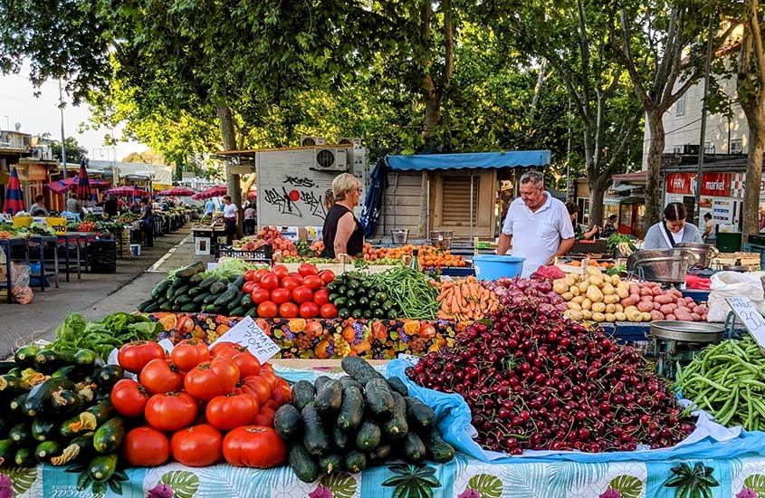 pessoas caminham em feira da Croácia, onde há barracas com tomates, cenouras e batatas disponíveis para compra